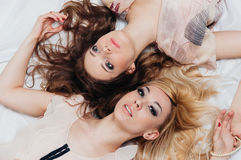 Two girls lie on the floor among accessories Royalty Free Stock Images