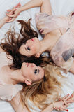 Two girls lie on the floor among accessories Royalty Free Stock Image