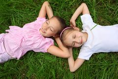 Two girls lie on grass with closed eyes Royalty Free Stock Photo