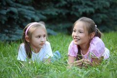 Two girls lie on grass in summer Royalty Free Stock Image