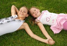 Two girls lie on green grass Stock Photos