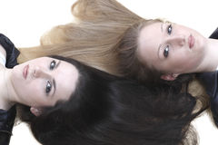Two girls lie with her hair Stock Photography