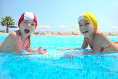 Two girls lie in pool and laugh Royalty Free Stock Photo