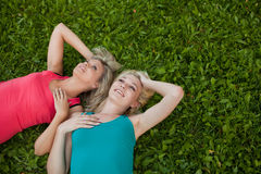 Two girls lie together on the grass and enjoy Royalty Free Stock Photo