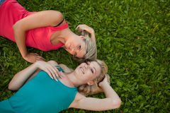 Two girls lie together on the grass and enjoy Stock Photos