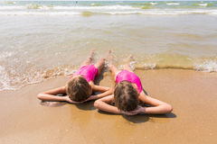 Two girls lie on your back on sandy beach and looking at sea. Two girls lie on your back on the sandy beach and looking at sea Royalty Free Stock Images
