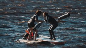 Two girls in life vests fighting with soft bats surfing boards in water. Two girls in life vests and swimming suits standing on surfing boards in water, fighting stock video footage