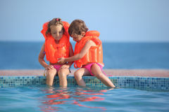 Two girls in lifejackets sitting on ledge pool