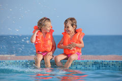Two girls in lifejackets sitting on ledge pool. Two little girls in lifejackets sitting on ledge pool on resort, Looking against each other royalty free stock image