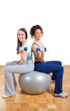 Two girls lifting weights sitting on ball Stock Photos