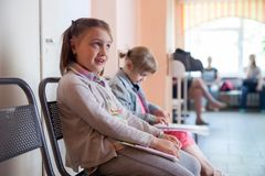 Sisters in   hospital   waiting for   doctor. Two girls in line in   doctor`s office in   clinic royalty free stock images
