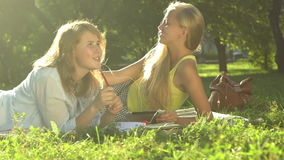Two girls listening to music in the park. Earphone, headphones, grass, meadow. Slow motion. Camera moving by slider stock footage