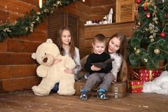 Two girls and a little boy are sitting on the floor against a wooden wall. Near the Christmas tree and gifts with a big teddy bear, next is an old suitcase Royalty Free Stock Photography