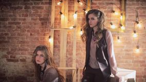 Two girls in the loft interior. Brick wall. Lamps, wooden frames and cubes stock video