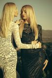 Two girls with long blond hair in lace dresses. Two girls with long blond hair in lace black and white dresses hugging on sunny day on natural landscape. Fashion royalty free stock photos