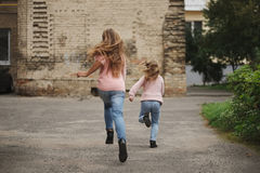 Two girls with long hair running away Stock Photography