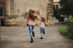 Two girls with long hair running away Royalty Free Stock Images