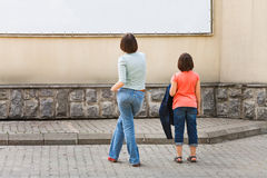 Two girls look at advertising banner Stock Photos