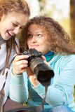 Two girls look through pictures on Royalty Free Stock Images