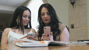 Two girls look at pictures on mobile phone in cafe stock footage