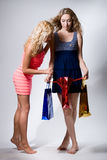Two girls look in a red paper package Royalty Free Stock Image