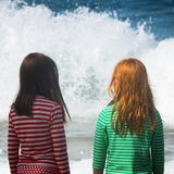 Girls Watch Big Waves Crash On Shore California. Two Girls Look At the Sea with Big Waves Stock Photos