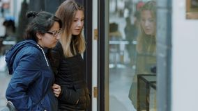 Two girls look a shop windows on a shopping mile. Travel photography stock video footage