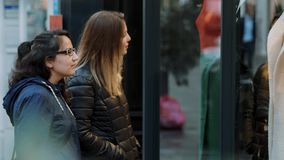 Two girls look a shop windows on a shopping mile. Travel photography stock video