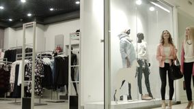 Two girls look at a show-window of shop. Two girls look at a show-window of clothes shop stock video