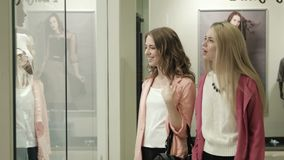 Two girls look at a show-window of shop. Two girls look at a show-window of clothes shop stock video footage
