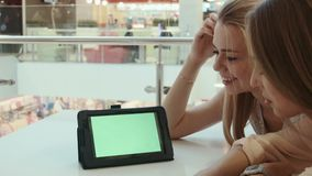 Two girls look at the tablet with the green screen. In mall stock footage
