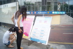 The two girls look at the want ads looking for a job. In Chinese Shenzhen Baoan Xixiang royalty free stock photography
