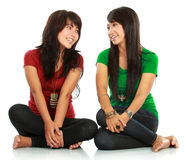 Two girls looking each other. Portrait of attractive two girls laughing looking each other on white background Stock Images
