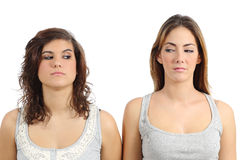 Two girls looking each other angry. Isolated on a white background Royalty Free Stock Photography