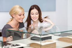 Two girls looking at glass case with jewelry Royalty Free Stock Image