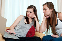 Two girls looking at a lap top. Royalty Free Stock Images