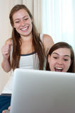 Two girls looking at a lap top. Royalty Free Stock Image
