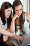 Two girls looking at a lap top. Royalty Free Stock Photography