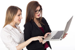 Two girls looking at a lap top Stock Image