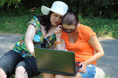 Two girls looking at laptop. Two beautiful girls looking at laptop computer outdoors Royalty Free Stock Images