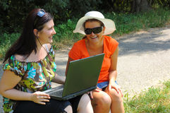 Two girls looking at laptop. Two beautiful girls looking at laptop computer outdoors Stock Photo