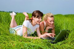Two girls looking at laptop computer. Two beautiful girls in white clothes are laughing and looking at laptop computer outdoors. Lay on the green grass Royalty Free Stock Image