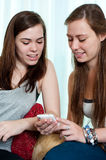 Two girls looking at mobile phone Royalty Free Stock Images
