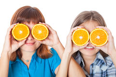 Two girls are looking through oranges Stock Images