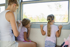 Two girls looking out of the window while sitting in an electric train until my mother combs long hair of one of them Royalty Free Stock Photo