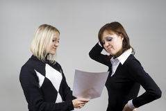 Two girls looking at the paper. On the background Stock Images