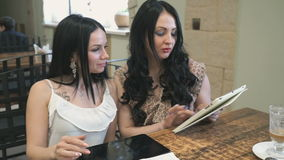Two girls looking at pictures on electronic tablet stock video footage