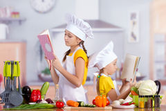 Two girls looking for a recipe in the book Royalty Free Stock Images
