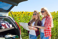 Two girls looking road map standing sunflowers field outdoor Royalty Free Stock Images