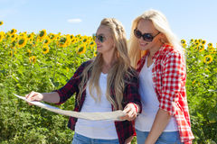 Two girls looking road map standing sunflowers field outdoor. Friends near car summer day holiday trip Royalty Free Stock Photo